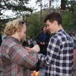 Liam presenting a braided cedar bracelet to a graduating ambassador.